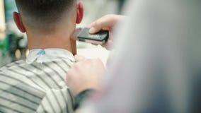 Ciérrese encima del corte de pelo masculino con la maquinilla de afeitar eléctrica Peluquero profesional que corta la máquina de  metrajes