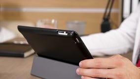 Ciérrese encima del doctor que sostiene una tableta digital en la tabla almacen de video