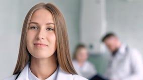 Ciérrese encima del especialista de sexo femenino bastante médico del retrato que sonríe y que presenta en el ambiente típico del almacen de video