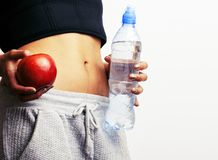 Ciérrese encima del estómago de la mujer con las manos que sostienen el agua y la manzana del registro Fotografía de archivo libre de regalías
