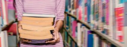Ciérrese encima del estudiante joven que lleva una pila pesada de libros Fotos de archivo