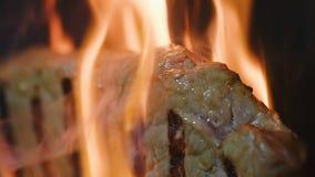 Ciérrese encima del filete macro de la carne de la falta de definición que cocina en parrilla del fuego almacen de video