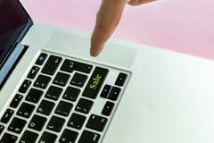 Ciérrese encima del finger de la mano del ` s de la persona que empuja el texto del ` de la venta del ` en un botón del concepto  imagen de archivo libre de regalías