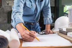 Ciérrese encima del funcionamiento del hombre del arquitecto que bosqueja un proje de la construcción Imágenes de archivo libres de regalías