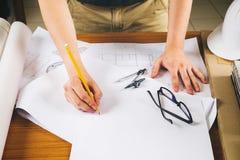 Ciérrese encima del funcionamiento del hombre del arquitecto que bosqueja un proje de la construcción Imagen de archivo libre de regalías