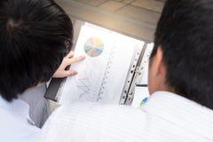 Ciérrese encima del gráfico entre los hombres de negocios, concepto de la reunión de negocios Imagen de archivo libre de regalías
