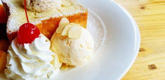 Ciérrese encima del helado de la vainilla, crema azotada blanca con la cereza roja en el top y la tostada borrosa de la mantequil imagen de archivo