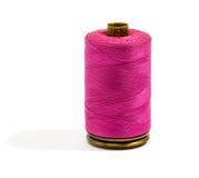 Ciérrese encima del hilo rosado oscuro del algodón en un carrete Imágenes de archivo libres de regalías