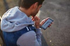 Ciérrese encima del hombre joven hermoso que usa el teléfono elegante mientras que se coloca al aire libre en la tarde soleada Foto de archivo