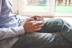 Ciérrese encima del hombre polivalente de las manos que usa la tableta fotografía de archivo