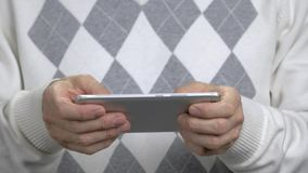 Ciérrese encima del hombre que juega en su smartphone almacen de video
