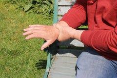 Ciérrese encima del hombre que lleva a cabo artritis dolorosa de la muñeca Fotos de archivo libres de regalías