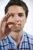 Ciérrese encima del hombre que muestra la píldora imagenes de archivo