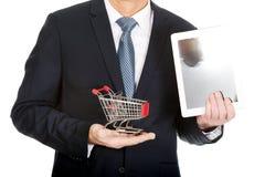 Ciérrese encima del hombre que sostiene el carro de la compra y la tableta Foto de archivo libre de regalías