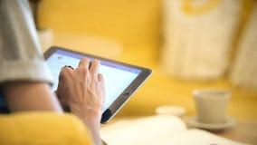 Ciérrese encima del hombre que usa la tableta en el café del café en la tabla almacen de metraje de vídeo