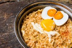 Ciérrese encima del huevo y de la yema de huevo de la sal con los tallarines picantes del estilo tailandés en la tabla Foto de archivo