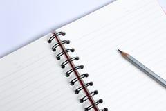 Ciérrese encima del lápiz con el cuaderno en la tabla blanca Fotografía de archivo
