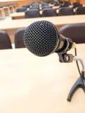 Ciérrese encima del micrófono en sala de conferencias del fondo imagenes de archivo