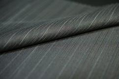 Ciérrese encima del negro del rollo del traje de la tela Foto de archivo