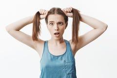 Ciérrese encima del retrato aislado de la muchacha caucásica encantadora divertida del estudiante con los ojos de siega del pelo  Imagen de archivo libre de regalías