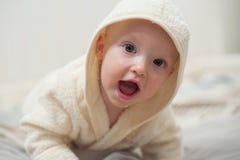Ciérrese encima del retrato del bebé divertido lindo en albornoz Imagen de archivo libre de regalías