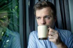 Ciérrese encima del retrato del café de consumición del hombre de negocios hombre que mira la ventana del canal y que sostiene la Imagen de archivo libre de regalías
