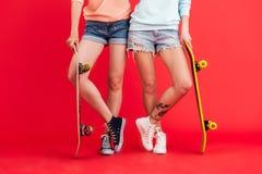 Ciérrese encima del retrato de dos chicas jóvenes en pantalones cortos del dril de algodón Fotos de archivo