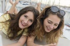 Ciérrese encima del retrato de dos novias emocionadas con los teléfonos móviles que se acuestan y que ríen y que miran in camera Imágenes de archivo libres de regalías