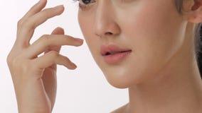 Ciérrese encima del retrato de la cara conmovedora de la mujer asiática joven hermosa y de la piel sana en concepto del skincare  almacen de metraje de vídeo