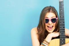 Ciérrese encima del retrato de la cara de la mujer joven con la guitarra Fotos de archivo