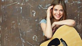 Ciérrese encima del retrato de la cara de la muchacha sonriente con la guitarra Imagen de archivo