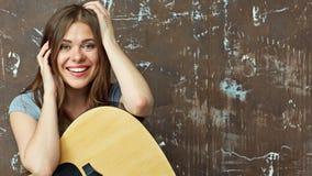 Ciérrese encima del retrato de la cara de la muchacha sonriente con la guitarra Imagenes de archivo