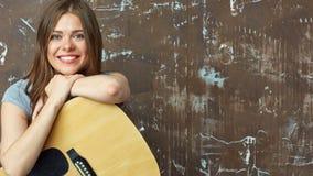 Ciérrese encima del retrato de la cara de la muchacha sonriente con la guitarra Imágenes de archivo libres de regalías