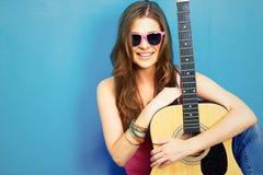 Ciérrese encima del retrato de la cara de la mujer joven con la guitarra Foto de archivo