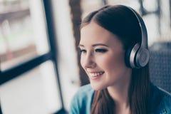 Ciérrese encima del retrato de la chica joven atractiva en auriculares modernos Imágenes de archivo libres de regalías