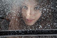 Ciérrese encima del retrato de la chica joven detrás de la ventana de la nieve del invierno en fondo oscuro Imagen de archivo libre de regalías