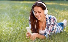 Ciérrese encima del retrato de la música que escucha de la chica joven bonita que miente en la hierba Fotos de archivo libres de regalías