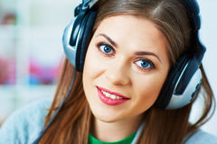 Ciérrese encima del retrato de la música que escucha de la mujer joven con el auricular Imagenes de archivo