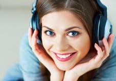Ciérrese encima del retrato de la música que escucha de la mujer joven con el auricular Fotografía de archivo