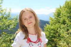 Ciérrese encima del retrato de la muchacha adolescente en camisa bordada con la montaña en el fondo Imagenes de archivo