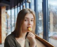 Ciérrese encima del retrato de la muchacha adolescente hermosa del estudiante con la piruleta en el café de la calle que se sient Foto de archivo libre de regalías
