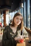 Ciérrese encima del retrato de la muchacha adolescente hermosa feliz del estudiante con un té de cristal de la fruta de la paja d Imagen de archivo libre de regalías
