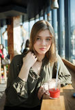 Ciérrese encima del retrato de la muchacha adolescente hermosa feliz del estudiante con un té de cristal de la fruta de la paja d Imagen de archivo
