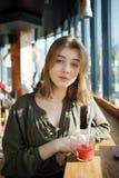Ciérrese encima del retrato de la muchacha adolescente hermosa feliz del estudiante con un té de cristal de la fruta de la paja d Imagenes de archivo