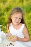Ciérrese encima del retrato de la muchacha adorable que come el desayuno y la leche de consumo al aire libre Cereal, forma de vid Fotografía de archivo