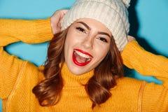 Ciérrese encima del retrato de la muchacha bastante alegre en sombrero del invierno Foto de archivo