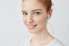 Ciérrese encima del retrato de la muchacha del pelirrojo con las pecas en auriculares que sonríe mirando la cámara Imágenes de archivo libres de regalías