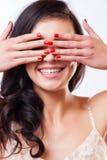 Ciérrese encima del retrato de la muchacha hermosa joven que se divierte y que oculta su cara con la mano Peinado natural del nud Foto de archivo
