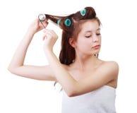 Ciérrese encima del retrato de la muchacha hermosa joven que tiene bigudíes de pelo en su cabeza Fotografía de archivo libre de regalías