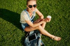 Ciérrese encima del retrato de la muchacha rubia joven con café y la tableta imagen de archivo